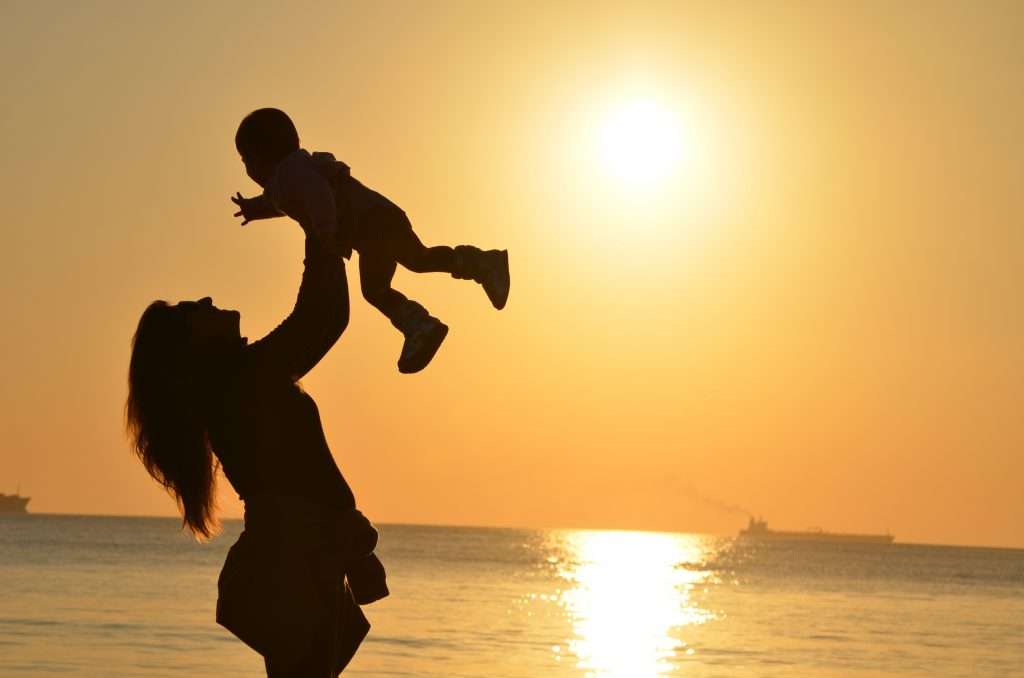 woman holding a baby on the beach at sunset